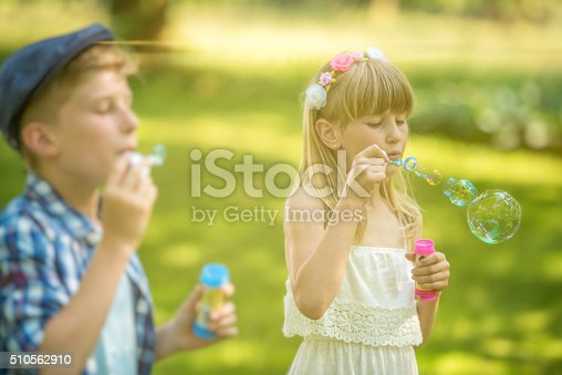 618034312 istock photo Boy and girl blowing soap bubbles 510562910