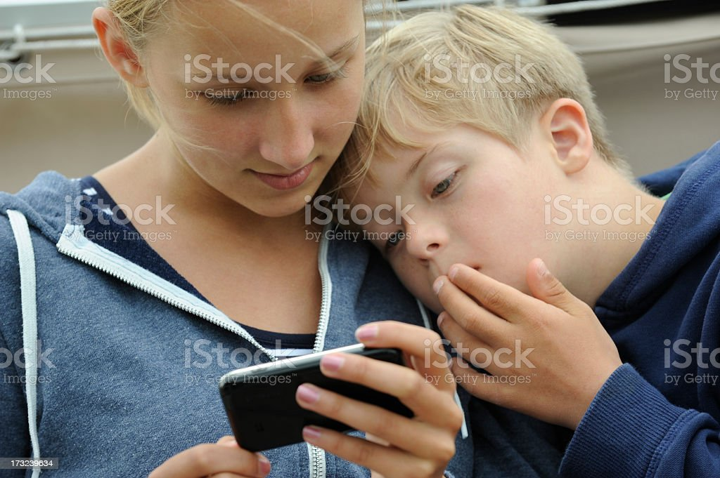 Boy and girl busy with mobile phone royalty-free stock photo