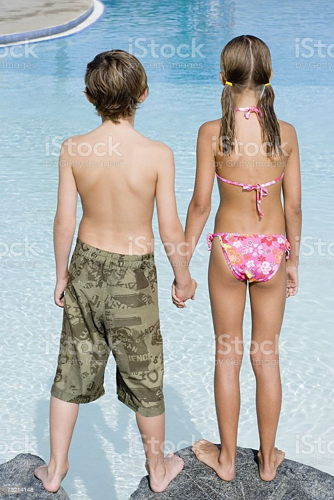 Boy and girl by swimming pool stock photo