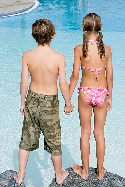 boy and girl by swimming pool - rear view stock photos and pictures