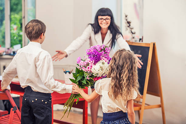 boy and girl children give flowers as a school teacher - teachers day stock photos and pictures