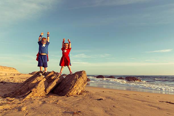 jungen und mädchen gekleidet wie superhelden auf california strand - traum team stock-fotos und bilder
