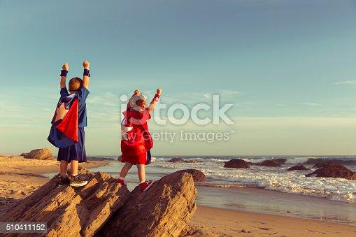 A young boy and girl dressed as a superheroes stands on a rock with arms raised while on a California Beach. The surf and waves wash the sand around them and they are ready to work as a team to accomplish great things as they look out to sea. Image taken in Orange County, California, USA.