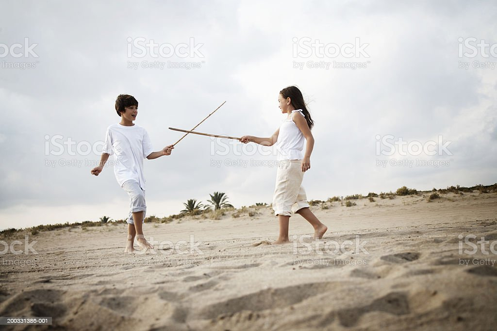 Boy and girl (8-10) duelling with pretend swords, low angle view stock photo