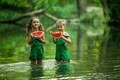 Boy and girl eating watermelon standing knee deep in the lake in the woods