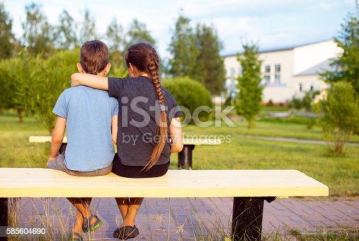 585604690istockphoto boy and girl embrace 585604690