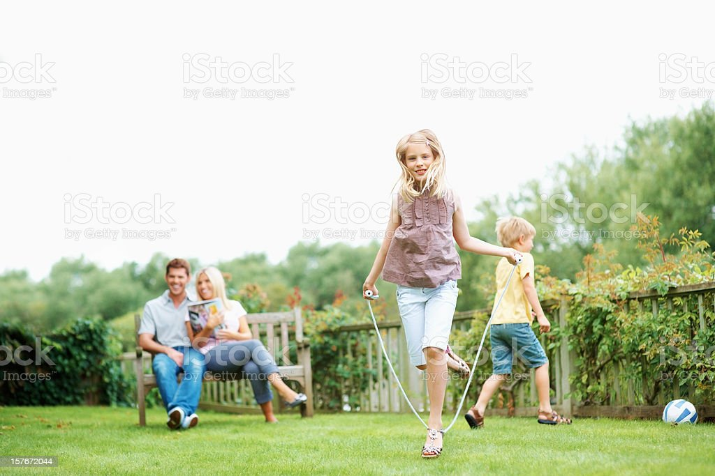 Boy and girl enjoying while parents sitting on bench royalty-free stock photo