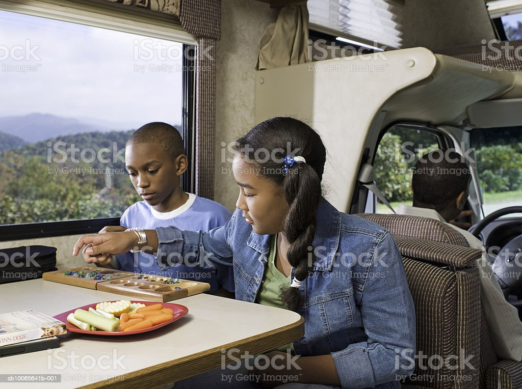 Boy (12-13) and girl (10-11) father driving foto royalty-free