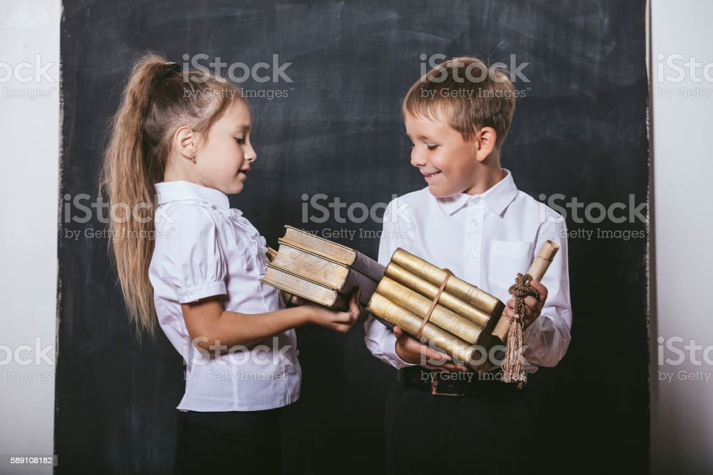 Boy and girl from elementary school  with books stock photo