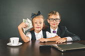 Boy and girl has earned a lot of money. Banker holds in hand American dollars. Smart business boy. Successful school children. Happy. Success concept. Business suit. Stock exchange. Lucky girl
