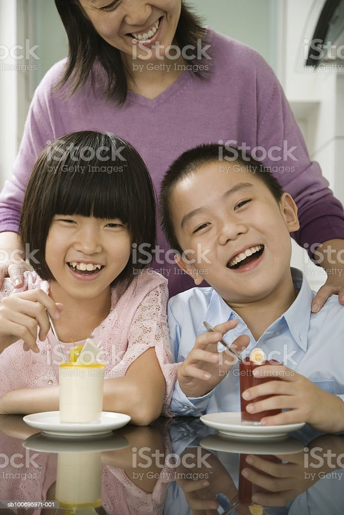 Boy (8-9) and girl (10-11) having breakfast with their mother standing behind them foto stock royalty-free