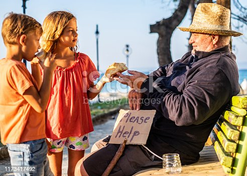 Homeless men asking for help and girl giving him a slice of bread