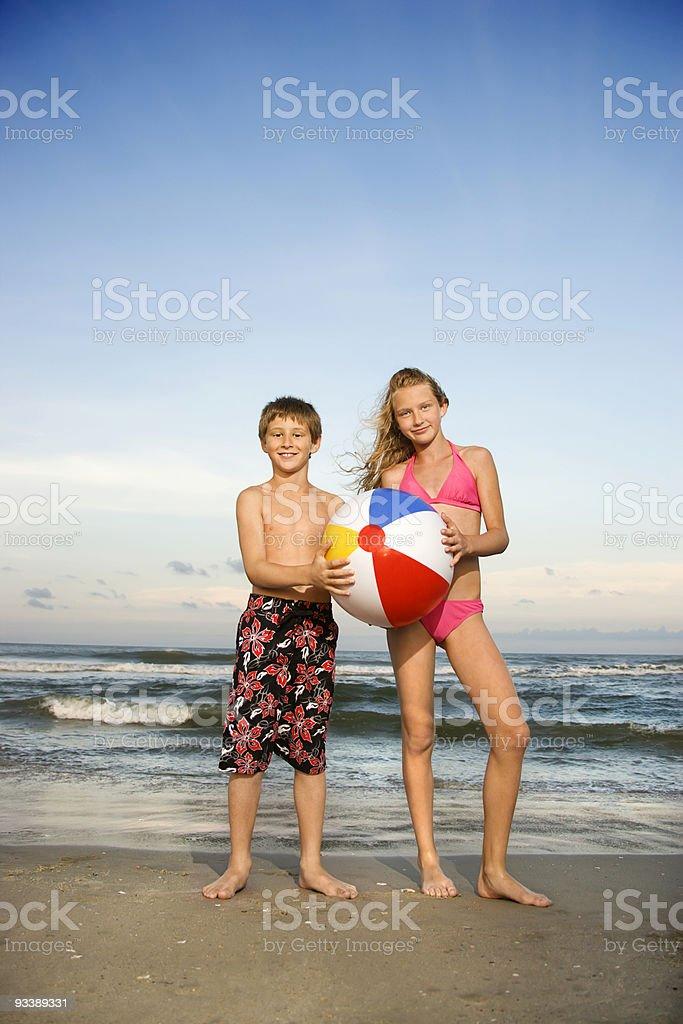Boy and girl holding beachball on beach. stock photo