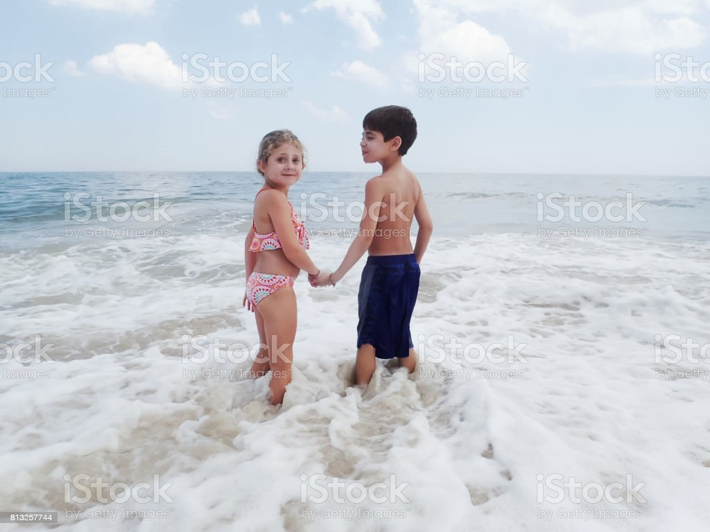 Boy and girl holding hands  in surf stock photo