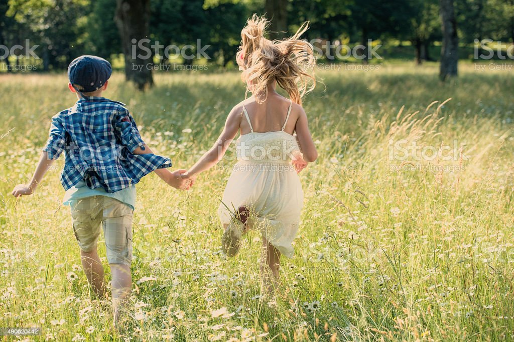 Boy and girl holding hands running across a meadow stock photo