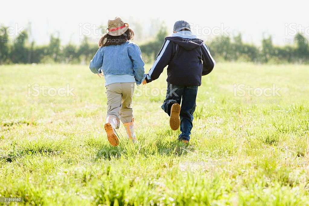 Boy and girl holding hands, running on field royalty-free stock photo