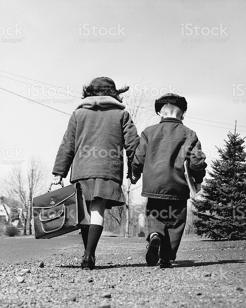Boy and girl holding hands, walking to school 免版稅 stock photo