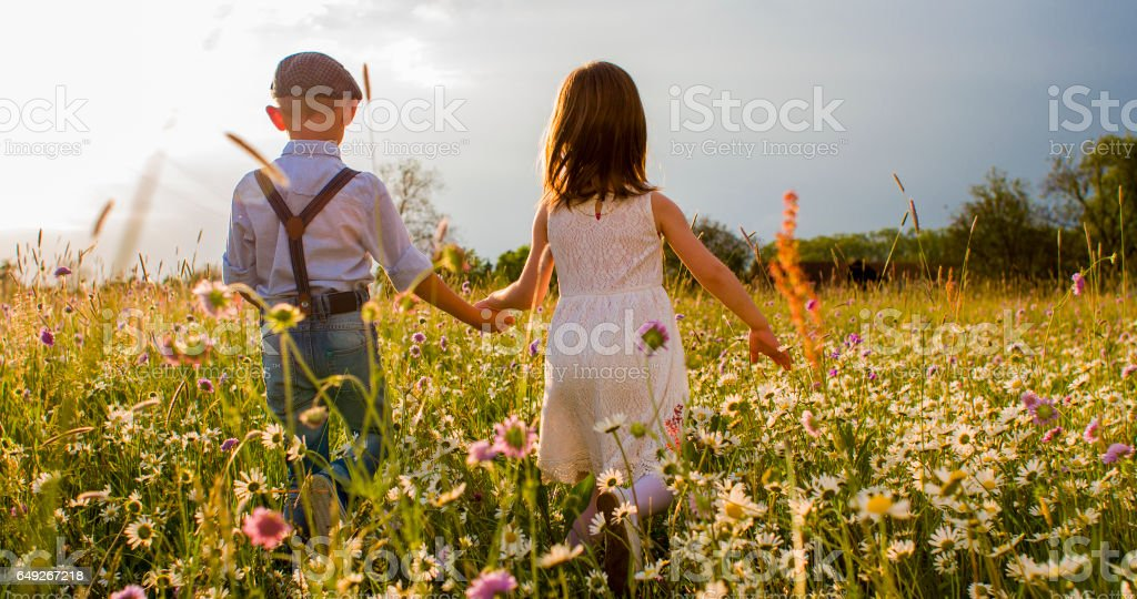Boy and girl holding hands while walking on meadow stock photo