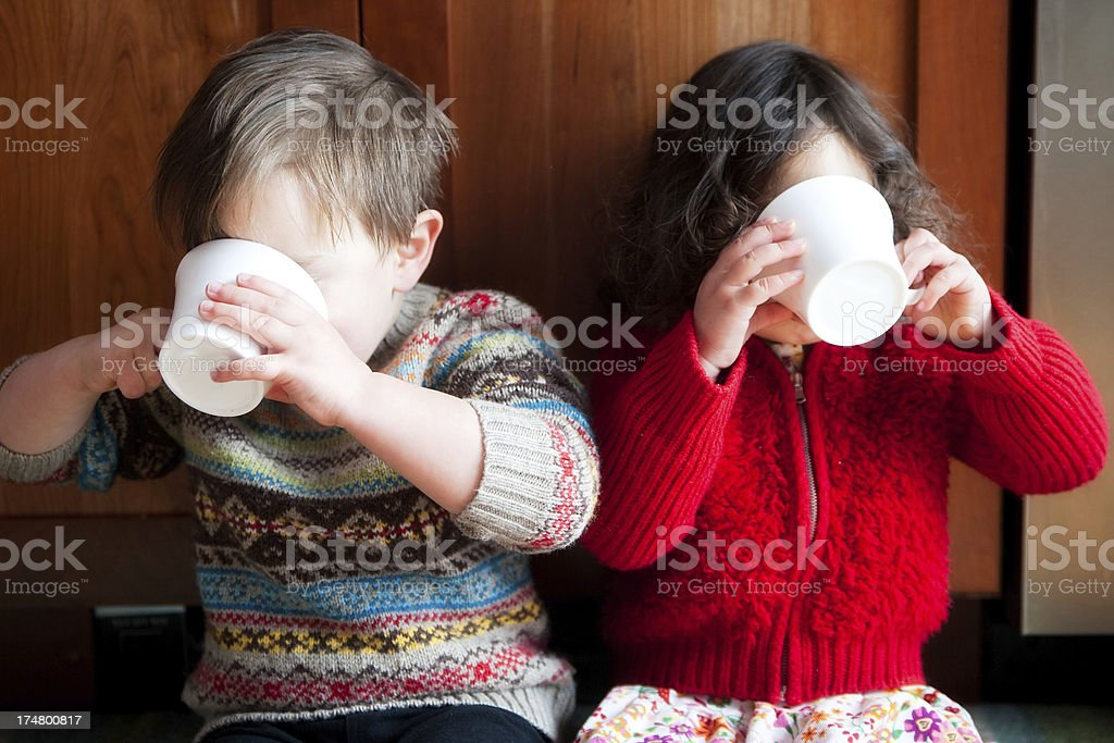 Boy and girl, in cute sweaters, sipping from white mugs stock photo