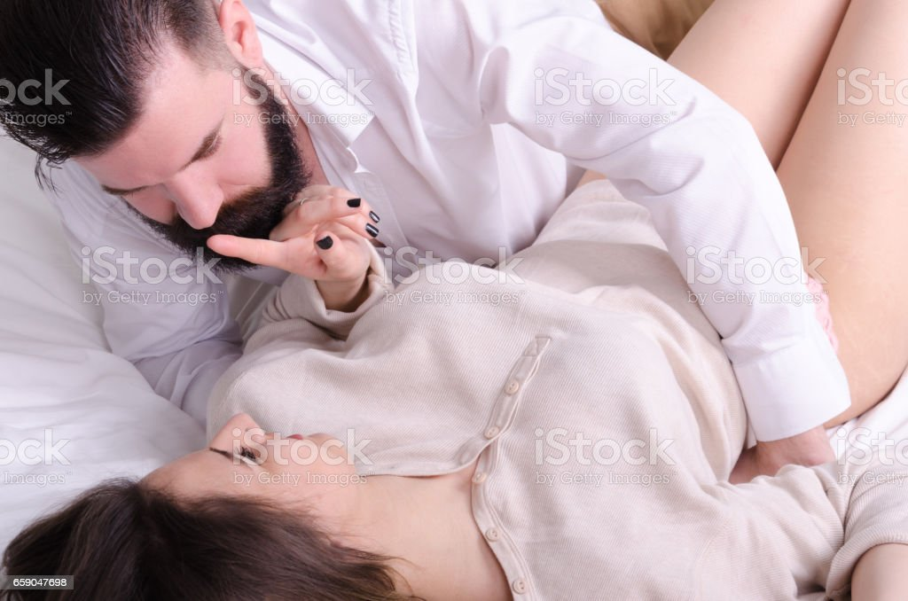 boy and girl in love roll on the bed and relax - foto de acervo