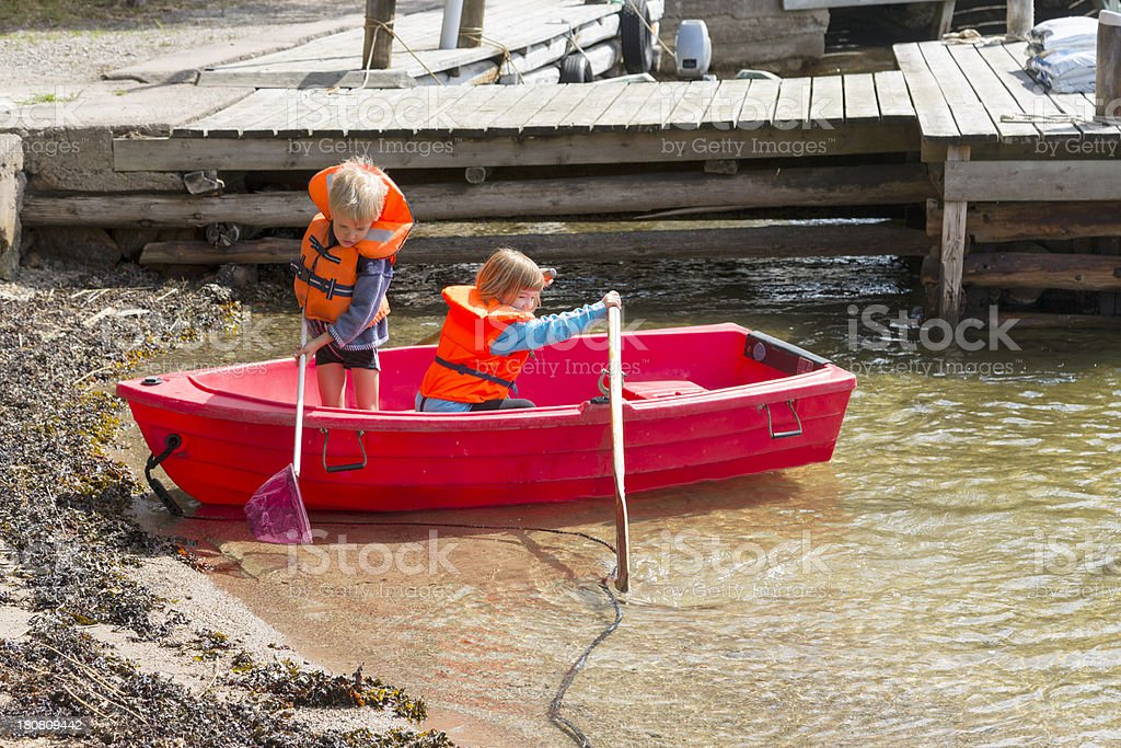Boy and girl in red rowing boat with life jackets royalty-free stock photo