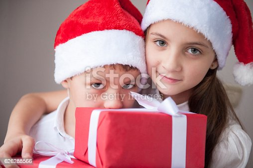 865399512 istock photo boy and girl in santa hat holding box with gift 626288566