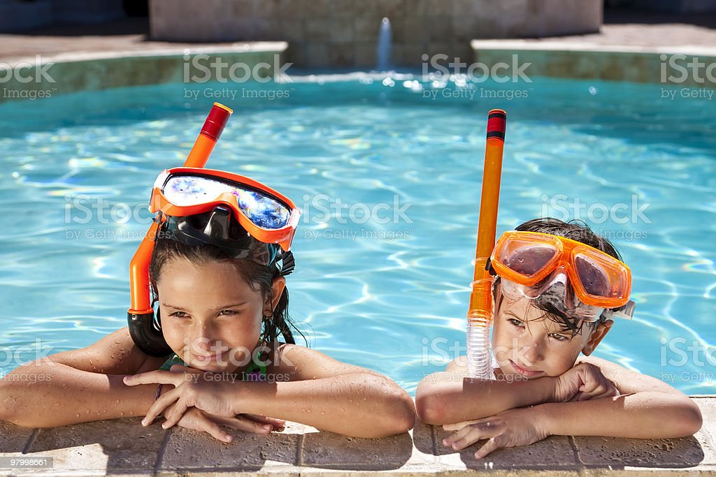 Menino e uma menina na piscina com óculos & Snorkel foto royalty-free