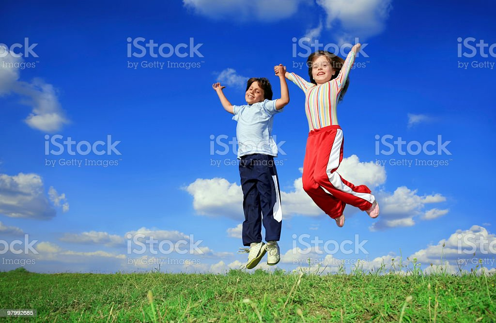 Boy and girl jumping with joy royalty free stockfoto
