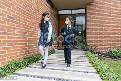 Happy Latin American boy and girl leaving their house and going back to school wearing facemasks to avoid te coronavirus - COVID-19 pandemic concepts