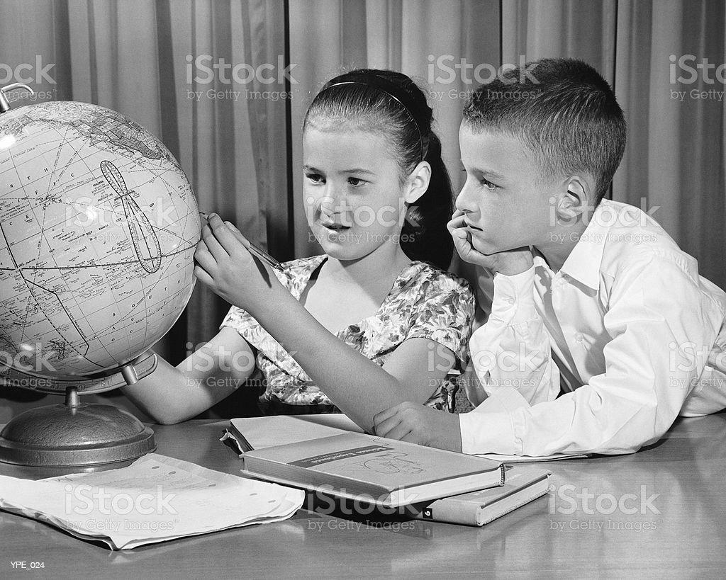 Boy and girl looking at globe royalty free stockfoto