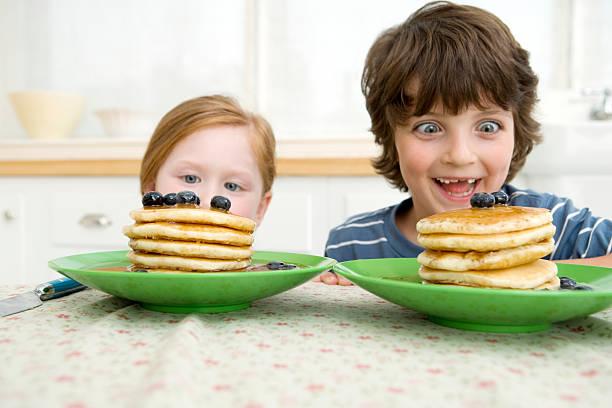 Jungen und Mädchen, die ein Pfannkuchen – Foto
