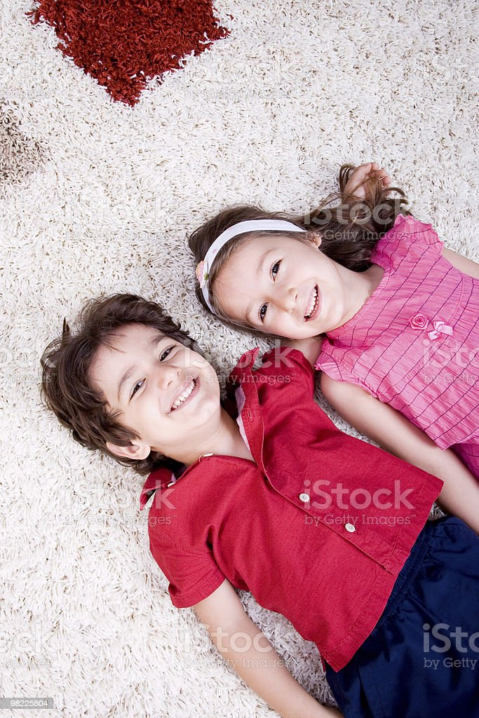 Boy and girl lying down on carpet royalty-free stock photo