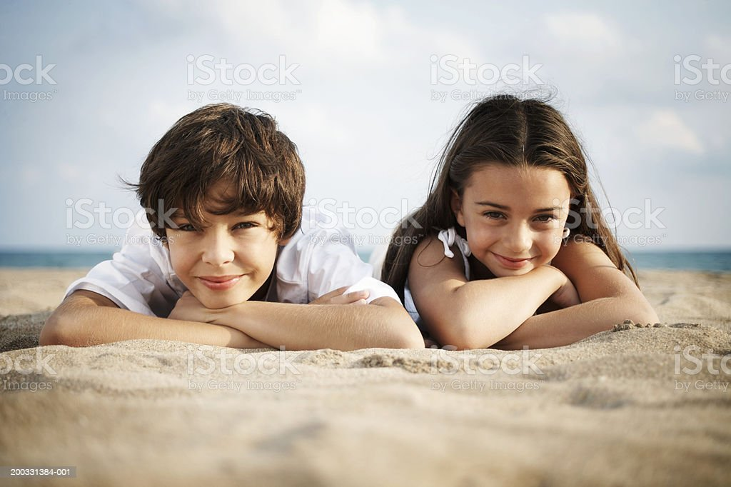Boy and girl (8-10) lying on beach, smiling, close-up, portrait stock photo
