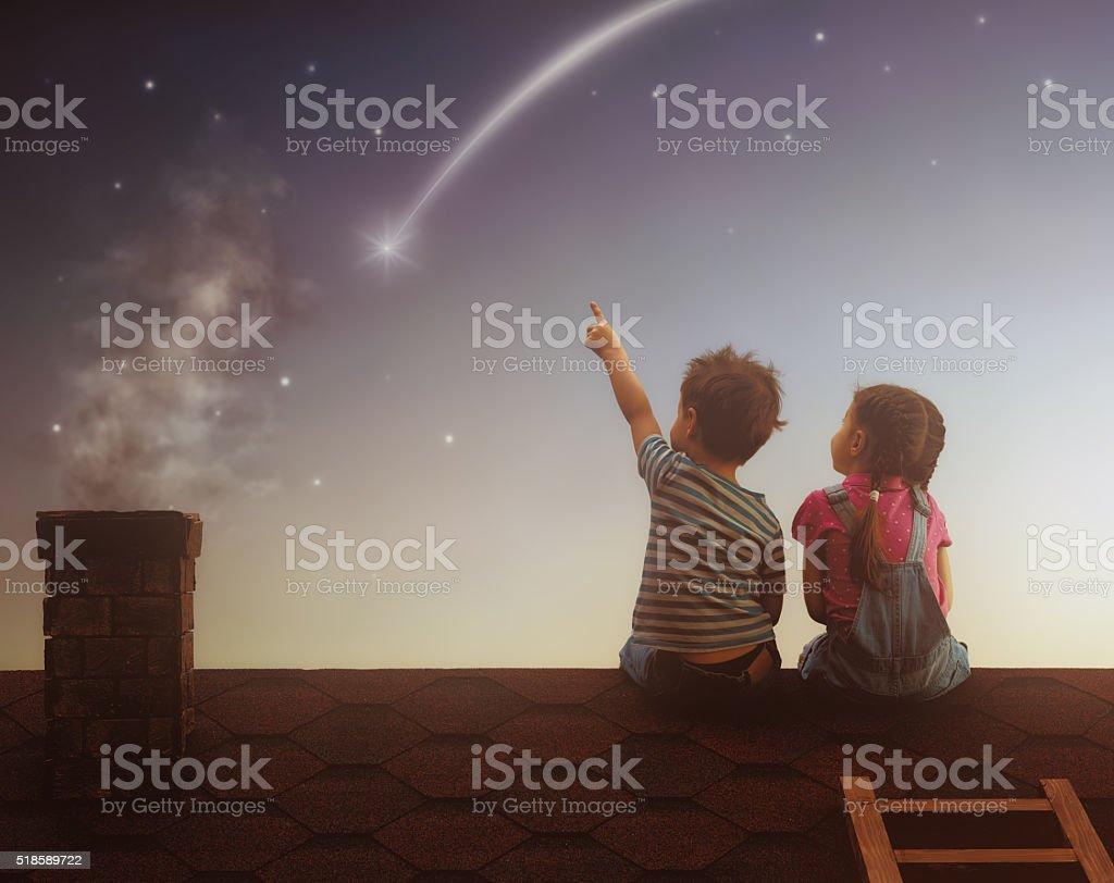 Menino e menina com fazer um desejo - foto de acervo