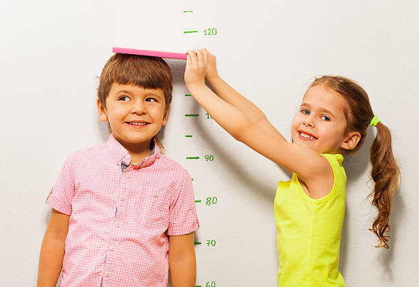 boy and girl measure height by wall scale at home - height measurement stock photos and pictures