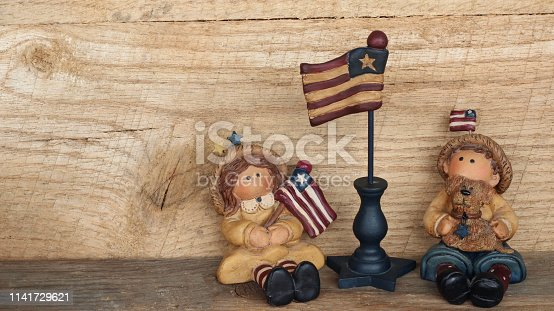 istock boy and girl next to american flag pole 1141729621