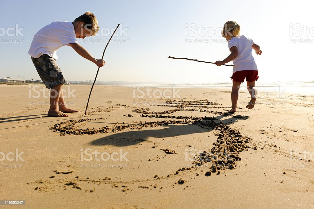 Boy and girl on beach writing in sand stock photo
