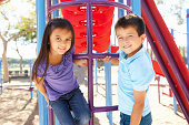 Boy And Girl On Climbing Frame In Park Smiling To Camera