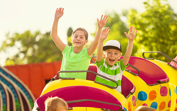 Boy and Girl on roller coaster ride at amusement park stock photo