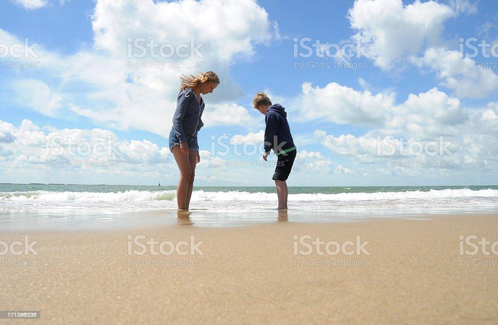 Boy and girl on the beach stock photo