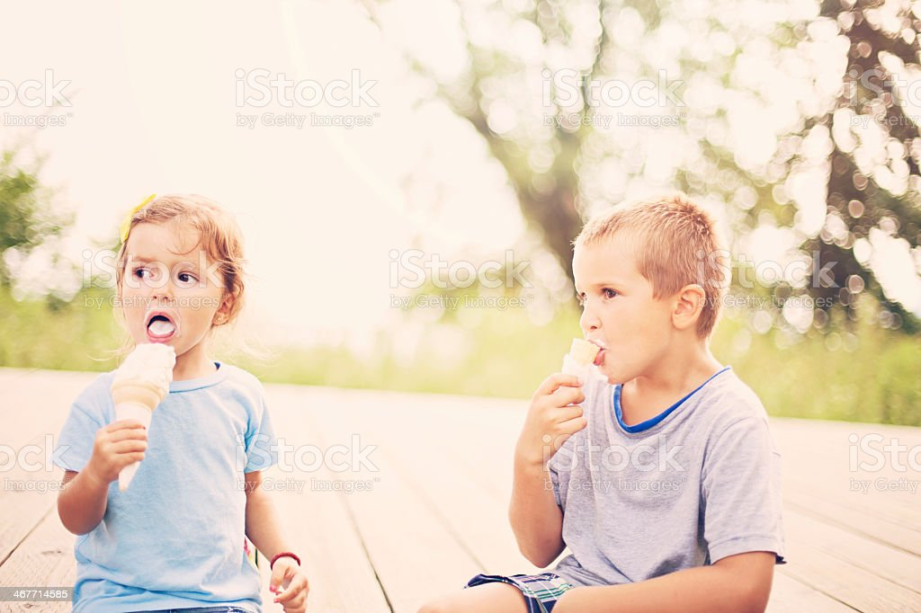 Boy and girl outdoors eating ice cream on bokeh background stock photo