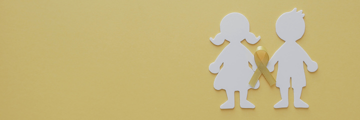 Boy and girl paper cut with yellow gold ribbon, Sarcoma Awareness, Bone cancer, childhood cancer awareness, World Suicide Prevention Day, September yellow