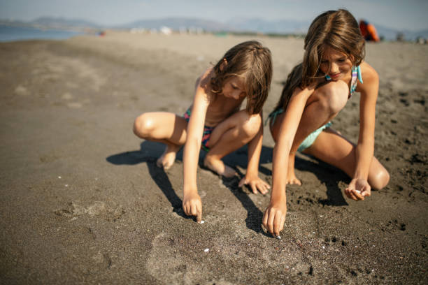 boy and girl picking up shells on the sand beach - little girl picking up sea shells at the beach stock pictures, royalty-free photos & images