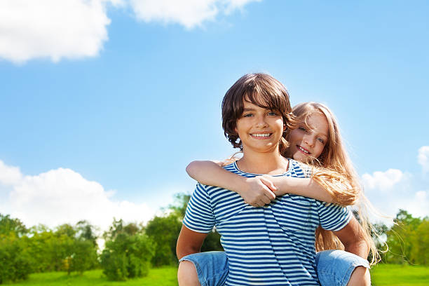 Boy and girl piggyback stock photo
