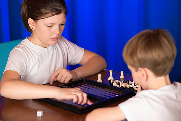 boy and girl playing a board game called backgammon - backgammon stock pictures, royalty-free photos & images