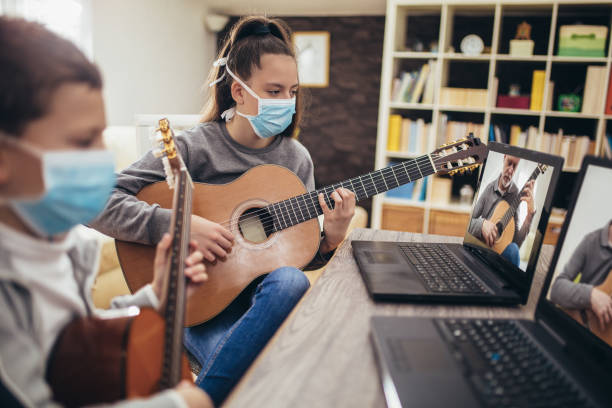Boy and girl playing acoustic guitar stock photo