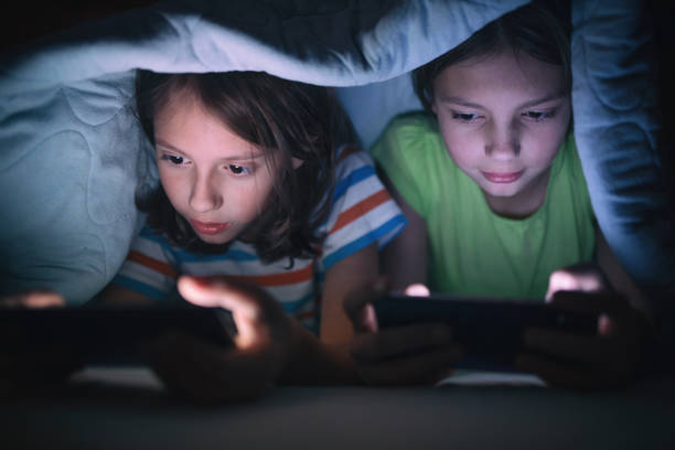 boy and girl playing games on mobile phone in their bed - smartphone addiction not groups stock pictures, royalty-free photos & images