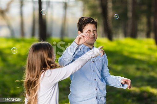 618034312 istock photo boy and girl playing in park with soap bubbles 1160234054