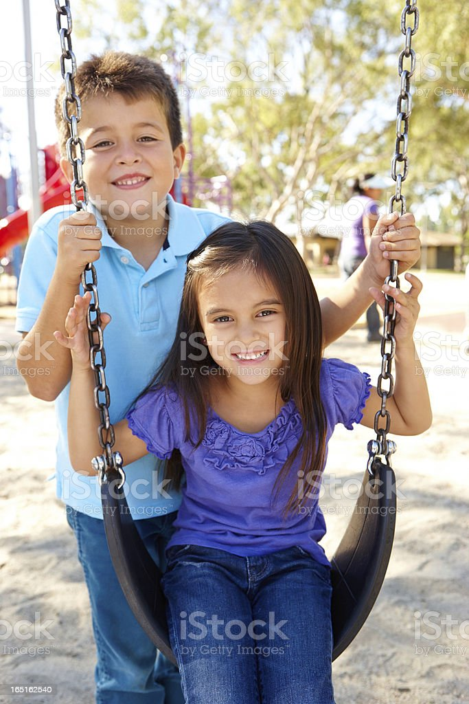 Boy And Girl Playing On Swing In Park royalty-free stock photo