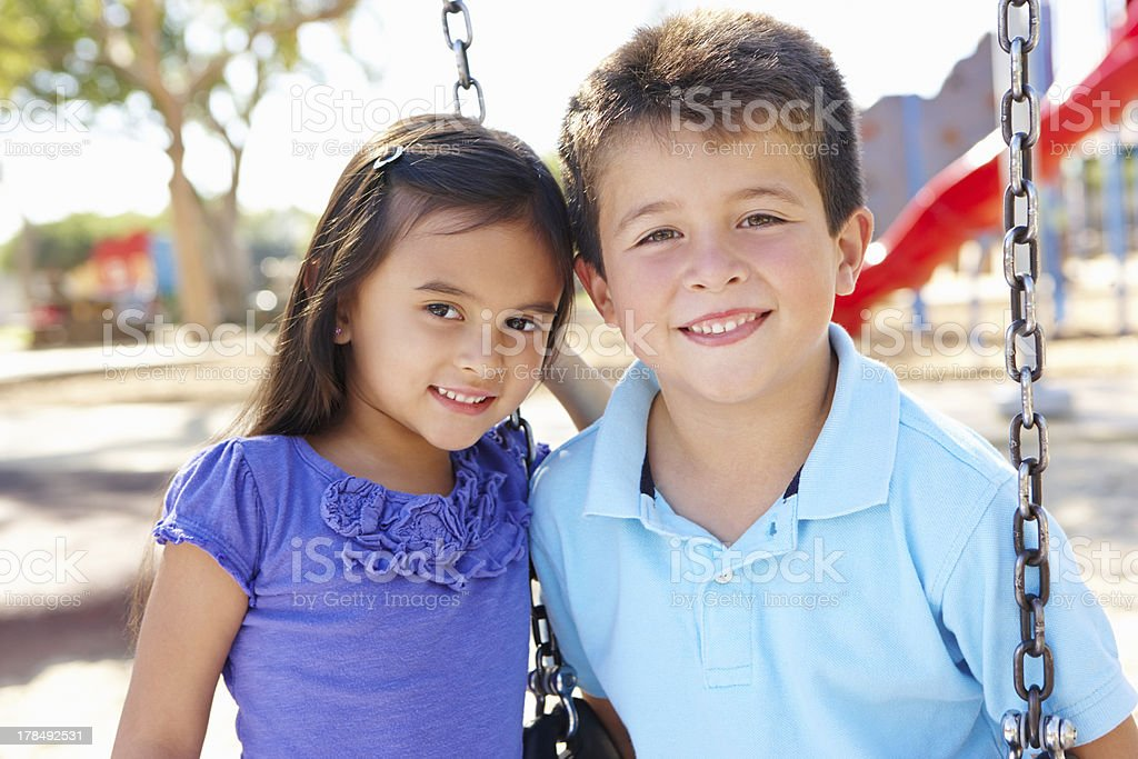 Boy And Girl Playing On Swing In Park stock photo